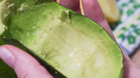 masa örtüsü : Guacamole recipe, first step. The hand pulls out a spoonful of avocado pulp, a static macro shot. Cooking a vegetarian breakfast with organic produce. Half of green juicy avocado fruit close up Stok Video