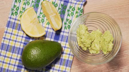 Guacamole recipe, final step. The chef puts the ready-made guacamole in a transparent plate, on a wooden background, a beautiful tablecloth and lemon slice. Healthy and organic natural food