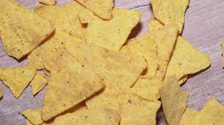 Nachos fall on a wooden board, close-up. Harmful Mexican snack, unhealthy fast food. Crispy, salty yellow corn triangles