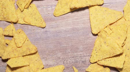 sağlıksız : Stop motion of nachos chips on a wooden background, copyspace for your text. Mexican snack close-up, harmful and caloric food