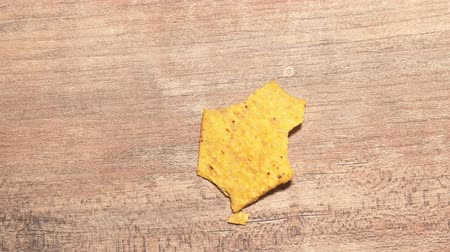 One yellow triangular nachos are eaten stop motion timelapse. Fast food and high-calorie food. Chips for snacking Wideo