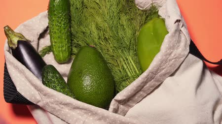 A man puts vegetables in a cotton bag on an isolated colored background. Cucumbers, tomatoes, avocados and other vegetables in a recycle cloth bag. Top view, static shot.