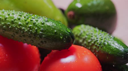 Cinematic drops fall and flow down on cucumbers and tomatoes, MACRO. Organically pure, farm vegetables close-up