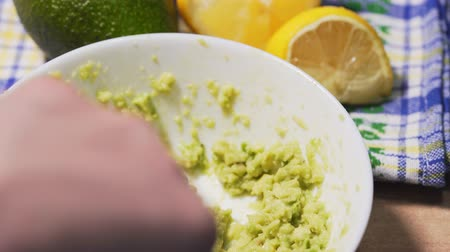 masa örtüsü : Cooking a traditional guacamole sauce on the table, close-up. Green raw avocado in a white bowl against a beautiful tablecloth