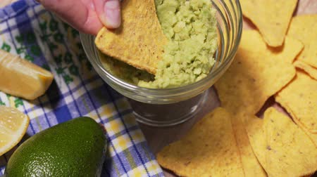 daldırma : Person eats guacamole with nachos chips at a party, close-up. Delicious snack for the company, vegetarian food