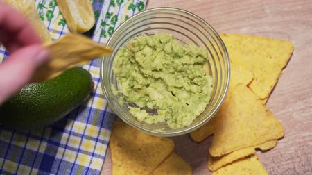 daldırma : The family eats traditional Mexican guacamole sauce with chips, top view. Vegan snack from unhealthy and healthy foods Stok Video