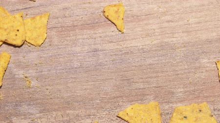 triângulo : Stop motion harmful fast food, Mexican corn chips taken from wooden table. Delicious yellow nachos chips are eaten