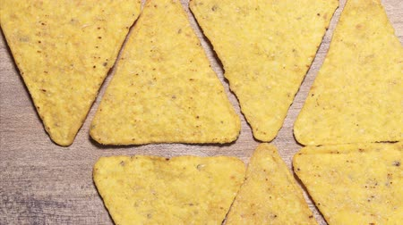 batatas : Stop motion movement the corn nachos chips on the table. Beautiful triangular traditional Mexican yellow snacks on a wooden table close-up Stock Footage
