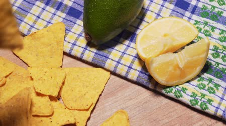 アボカド : Salted corn chips nachos poured on a wooden table, against the background of lemon and avocado. Tasty and harmful snack, fast food