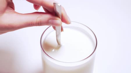 培養液 : The womans hand stirs farm yoghurt in a glass in circular motions with a spoon. Fresh soy milk in a transparent glass of white background isolated