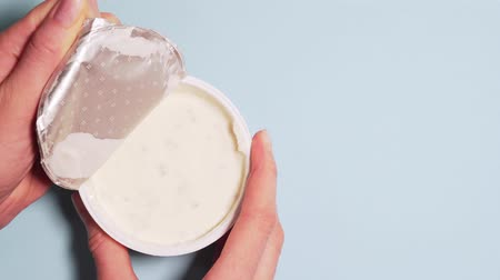 bactérias : Fresh organic yogurt for proper nutrition. Female hands slowly open the lid of yogurt, isolated on a white background Stock Footage