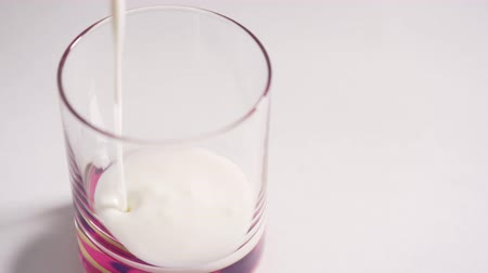 kalcium : A person pours homemade kefir into a glass. Milk quickly fills the glass on a white background Stock mozgókép