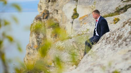 crevice : a man sits on the edge of the cliff slow motion