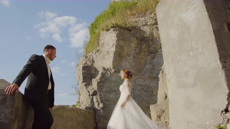 Young wedding couple posing on old stone stairs. Ruined antique castle