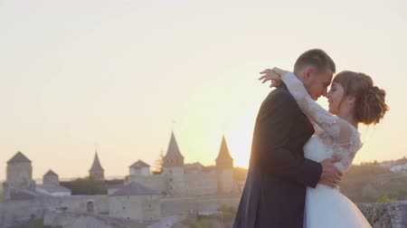 caresses : Lovely wedding couple kisses each other and embraces near the castle sunset