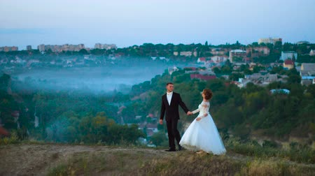 Young couple in love on a mountain meadow on the background of fog and city Stock Footage