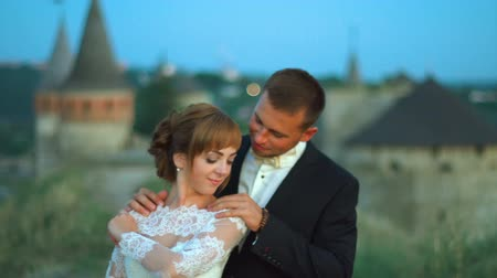 Lovely wedding couple kisses each other and embraces near the castle sunset