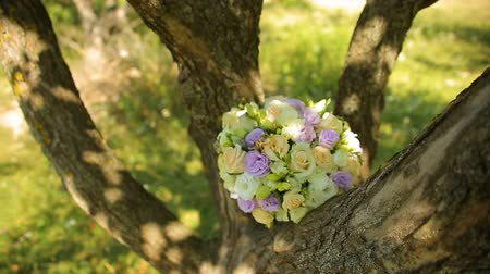Wedding Bouquet Tied With Ribbons to the Swings Under the Tree