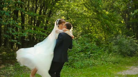 Happy groom and beautiful bride in white dress dancing in the green forest Stock Footage