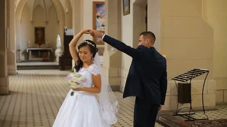 templombúcsú : Elegant bride and groom wearing blue suit holding hands walking in old church Stock mozgókép