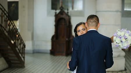 Elegant bride and groom wearing blue suit holding hands walking in old church Stock Footage