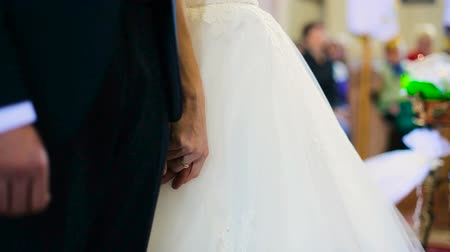 Groom in black suit holds brides hand tenderand says promise