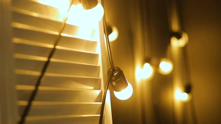 getting electricity : Light bulbs garland close up. Electric bulb shine hanging on wall as decoration Stock Footage