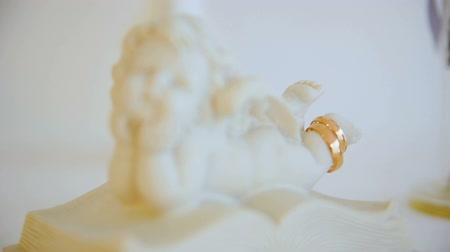 предъявитель : two wedding gold rings. angel figure statuette. angel on book. closeup Стоковые видеозаписи