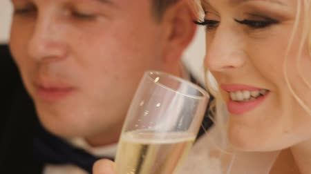 espartilho : Bride and groom pose to the photographer in studio near fireplace with champagne Stock Footage