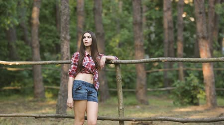 ranč : Young hot woman standing at fence. Cowgirl style outdoors Dostupné videozáznamy