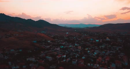 Mountains Peaks, Sunset Sea and the city. Epic on the edge of the mountain valley with rocks and sun flare. 4k drone flight. Aerial establisher, Koktebel. Europe green nature. Film vintage colors.