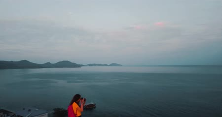 Mountains Peaks, Sunset Sea and young woman. Epic on the edge of the mountain valley with rocks and sun flare. 4k drone flight. Aerial establisher. Europe green nature. Film vintage colors.