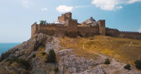Castle or Genoese fortress on top of the mountain. 4k drone flight. Aerial establisher. Film vintage colors. Great wall. Old historical architecture in Europe, Sudak. Deserted field and the sea.