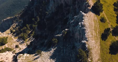 невозделанный : Mountains Peaks, Sunset and sea. Epic on the edge of the mountain valley with rocks and sun flare. 4k drone flight. Aerial establisher. Europe green nature. Film vintage colors. top view.