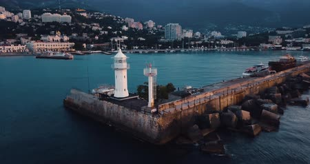 Lighthouse for ships and sunrise over the sea. Epic on the edge of the mountain valley. Sun flare. 4k drone flight. Aerial establisher. City by the ocean. Concept of marine travel. Film vintage colors