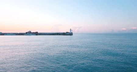 Lighthouse for ships and sunrise over the sea. Epic on the edge of the mountain valley and sun flare. 4k drone flight. Aerial establisher. Europe concept of marine travel. Film vintage colors.