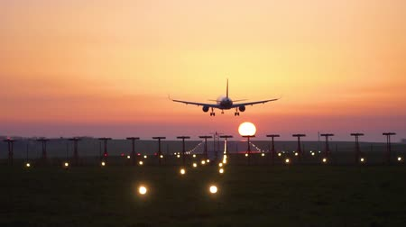 Airplane Landing on Airport Runway at Sunset, Beautiful Golden Sky