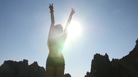Young Woman Having Fun Jumping in front of Sun, Silhouette