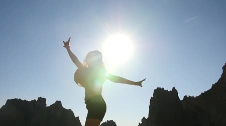 Young Woman Jumping in front of Sun, Silhouette 2