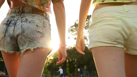 шорты : Two pretty girls in jeans shorts are walking in skate park, butts closeup Стоковые видеозаписи