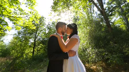 casamento : Bride and groom are kissing in beautifull green forest