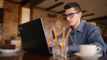 munka : Handsome freelancer businessman in glasses diligently working on laptop in cafe. Man typing on keyboard and searches new job on internet at coffeeshop. Business concept Stock mozgókép