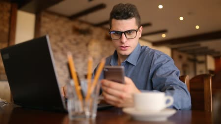 hipster : Handsome freelancer businessman in glasses diligently working on laptop in cafe is constantly distracting by annoying smartphone advertising notifications and messages. Business multitasking concept