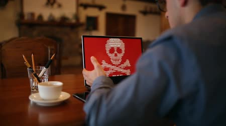 petya : Man with a laptop being infected by a ransomware spyware virus that is asking for money to retrieve the encrypted files. Scary red shimmering skull and crossbones on the screen.