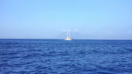 aegean sea : Boat is moving on the sea while there is a yacht on distance Stock Footage