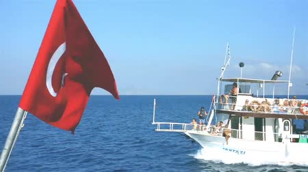 holiday makers : Turkish flag floats in mid air at the back of a boat
