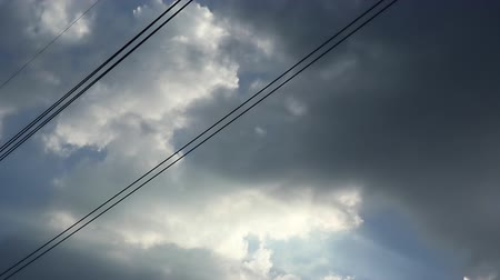 morbidezza : Gray overcast clouds on blue sky before rain or storm. Electrical power lines pass through the sky. Contrast between nature and technology.