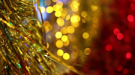 Christmas and New Year holiday celebration. Gold Christmas tinsel garland decorations blowing in the breeze. Blurred Christmas lights blinking in the background. Vídeos