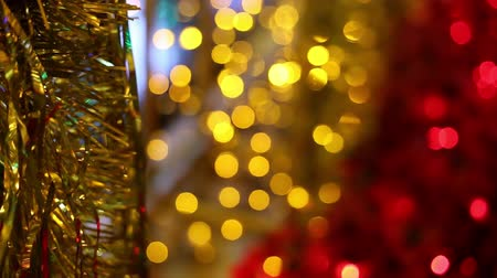 çelenk : Christmas and New Year holiday celebration. Gold Christmas tinsel garland decorations blowing in the breeze. Blurred Christmas lights blinking in the background. Stok Video