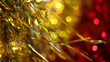 Christmas and New Year holiday celebration. Gold Christmas tinsel garland decorations blowing in the breeze. Blurred Christmas lights blinking in the background. Wideo